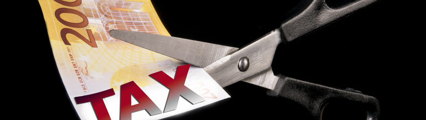 Scissors cut banknote, devaluation and tax concept. Isolated on black background. With copy space text. Studio Shot.